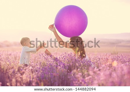 Mother and son playing with balloons on beautiful summer day - stock photo