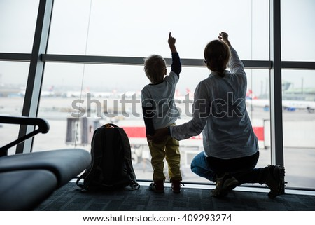 Mother and son pointing at taking off airplanes through window glass while waiting for their flight - stock photo
