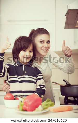 Mother and son preparing food in kitchen together - stock photo