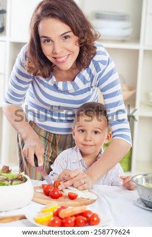 Mother and son preparing healthy meal together - stock photo