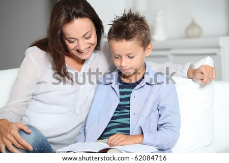 mother and son reading book on a sofa