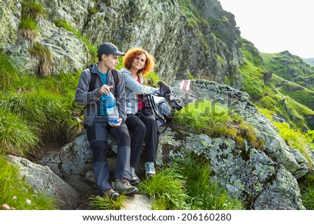 Mother and son resting after hiking over rocky mountains on a trail - stock photo