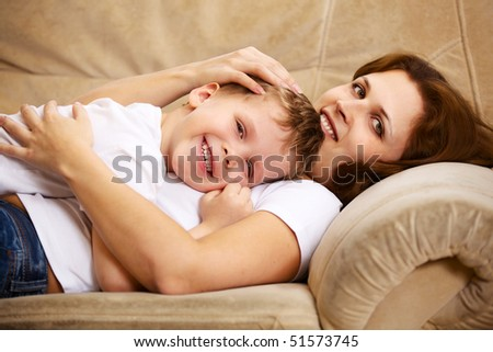 mother and son resting on sofa indoor