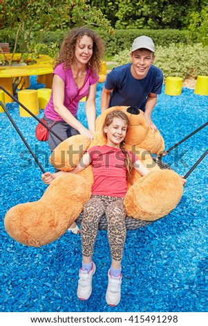 Mother and son rock junior sister on swings in summer park. - stock photo