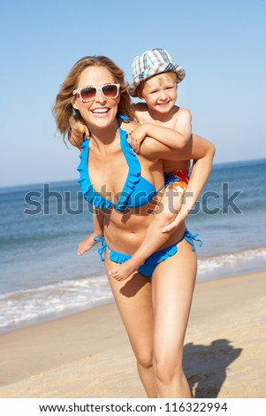 Mother And Son Running Along Beach - stock photo