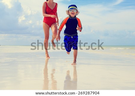 mother and son running in water on tropical beach - stock photo