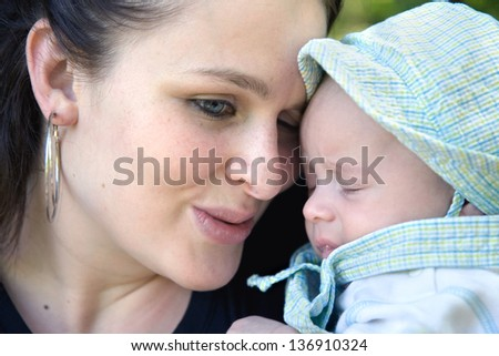 mother and son share a tender moment - focus on woman, baby spitting up - stock photo