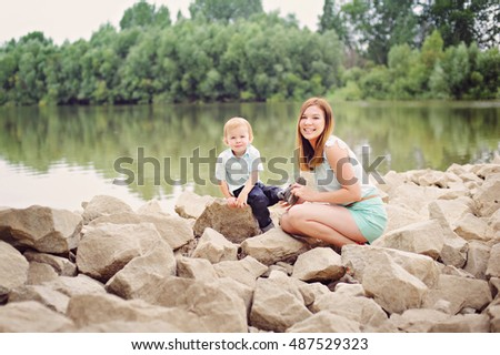 Mother and son sit on the stony banks of the river, full length.