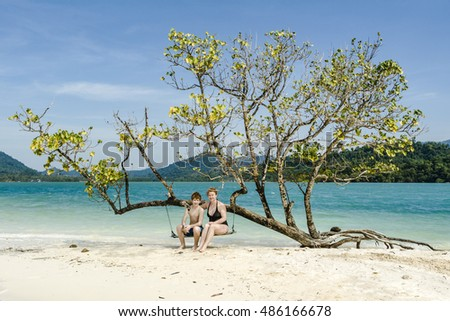 mother and son sitting on a beautiful swing, relaxing on a idyllic beach like paradise