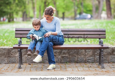 Mother and son sitting on a bench in a park and reading a book - stock photo