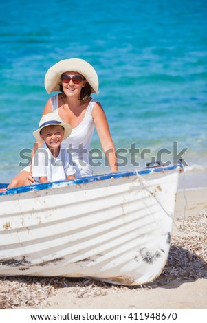 Mother and son sitting on a white boat at the tropical beach