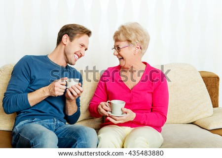 Mother and son sitting on couch and drinking tea or coffee - stock photo