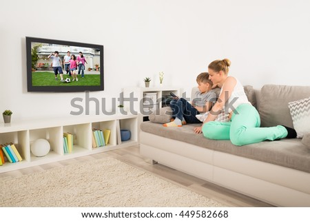 Mother And Son Sitting On Sofa Watching Television At Home