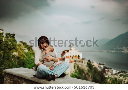 Mother and son sitting on stone back by the lake. Summer evening, calm relaxing atmosphere. Happy woman with her baby boy under the rainbow