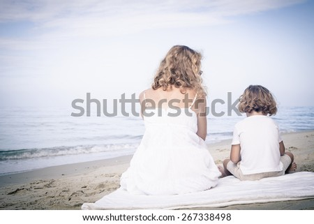 Mother and son sitting on the beach at the day time. - stock photo