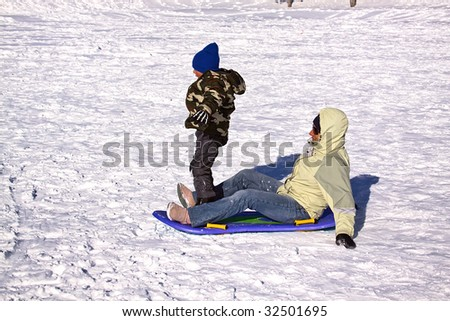 Mother and Son Sledding down the Hill while the Boy Trying to Stand Up