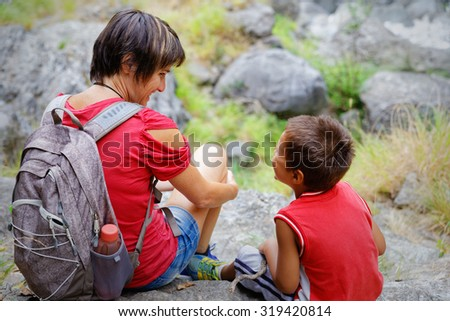 Mother and son smiling in a break during a hike in the mountains - stock photo