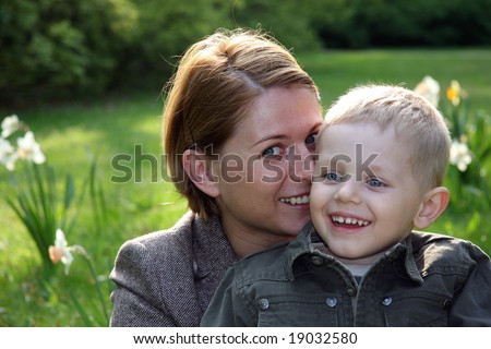 Mother and son smiling in spring scenery - stock photo