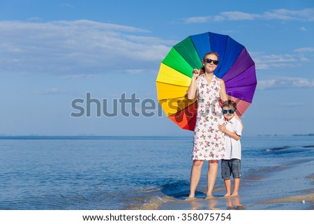 Mother and son standing on the beach at the day time. Concept of friendly family. - stock photo