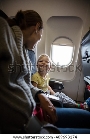 Mother and son talking and laughing on board of plane - stock photo