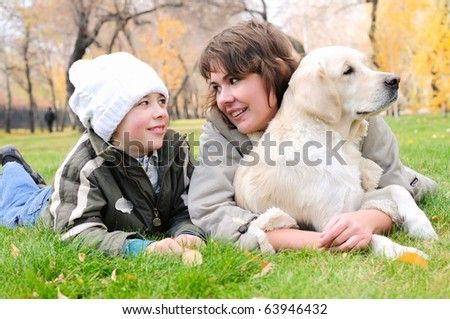 Mother and son together having fun in the autumn park playing with a golden retriever. - stock photo