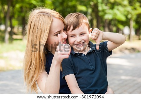 Mother and son together outdoors show thumb and say that everything is fine or not - stock photo