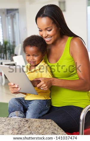 Mother And Son Using Digital Tablet In Kitchen Together - stock photo