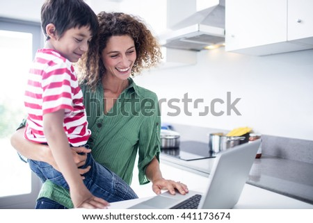 Mother and son using laptop in kitchen at home - stock photo