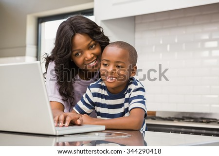 Mother and son using laptop in the kitchen - stock photo