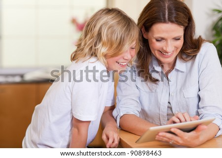 Mother and son using tablet together - stock photo