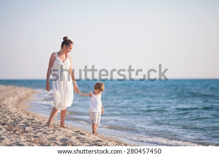 Mother and son walking along beach - stock photo