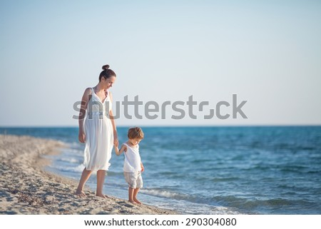 Mother and son walking along beach looking at the sea - stock photo