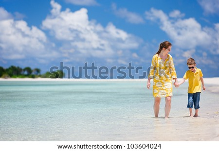 Mother and son walking along the tropical beach - stock photo