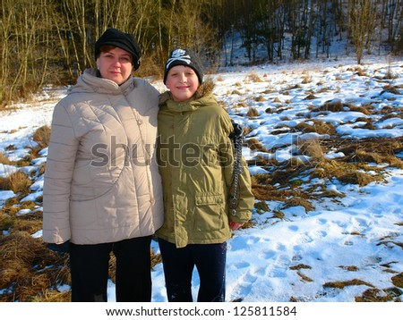 Mother and son walking in a winter forest - stock photo