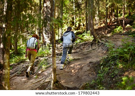 Mother and son walking on a hike trail in a forest