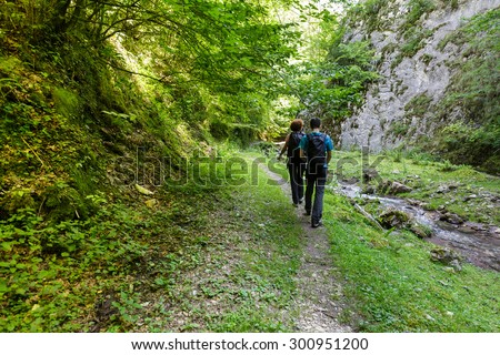 Mother and son walking on a mountain trail along a river - stock photo
