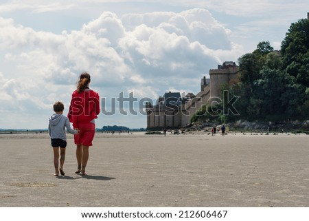 Mother and son walking on the beach in front of Mont Saint Michel ancient village. Normandy, France.