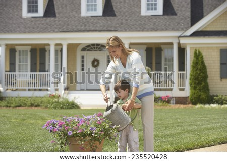 Mother and Son Watering Plant in Front of Their Home - stock photo