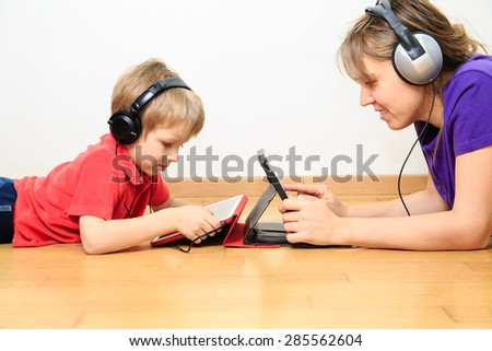 mother and son with headset looking at touch pad, modern technology - stock photo