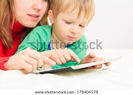 mother and son with touch pad at home, family leisure
