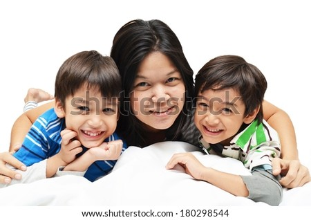 Mother And Sons Lying In Bed Together