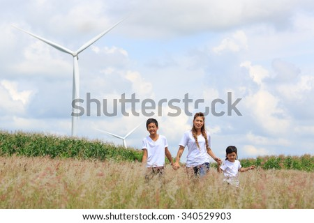 Mother and sons walking in field with huge wind turbine in background