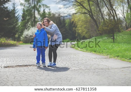 Mother and sun walking in the park during early spring time