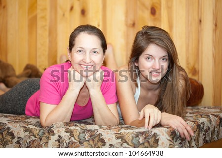 Mother and teen daughter laying on sofa at home - stock photo