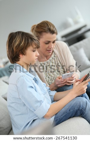 Mother and teenage boy playing with smartphone - stock photo