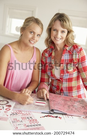 Mother and teenage daughter scrapbooking - stock photo