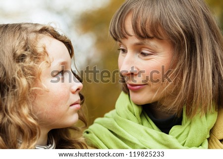 Mother and teenager daughter looking at each other while walking in an autumn park