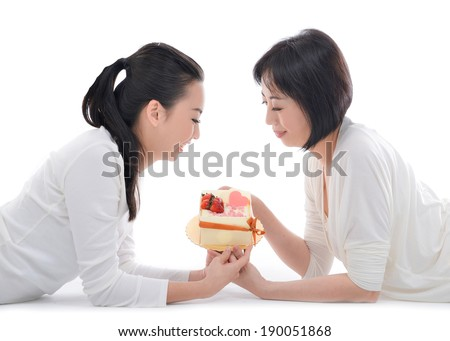 Mother and teenager daughter lying down holding cake over white background - stock photo