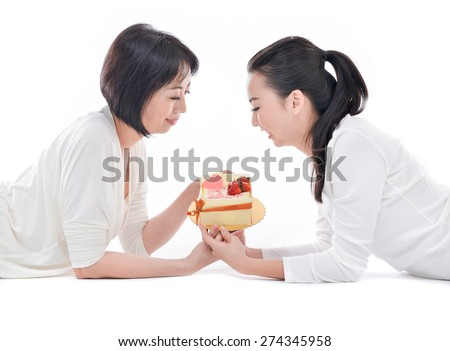 Mother and teenager daughter lying down holding cake over white background