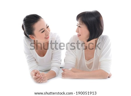 Mother and teenager daughter lying down over white background